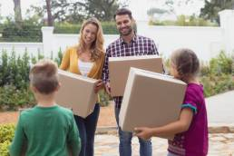 Front view of happy Caucasian family holding cardboard boxes in home yard