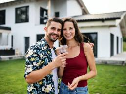 Portrait of young couple with wine outdoors in backyard, looking at camera
